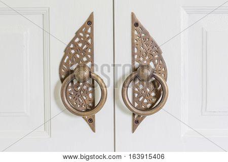Brass door handle on the white door