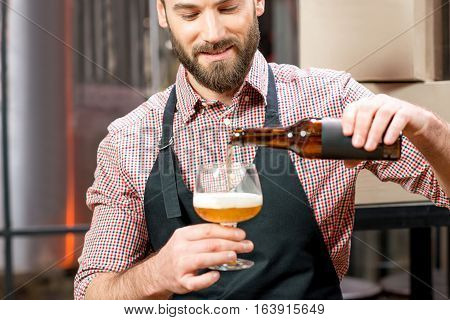 Handsome brewer in apron and shirt pouring beer into the glass at the manufacturing. Image focused on the brewer