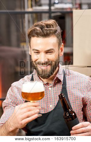 Handsome brewer expertising beer in the glass at the manufacturing