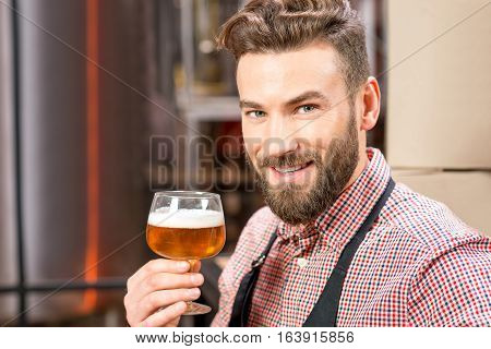 Portrait of smiling brewer with glass of beer at the manufacturing
