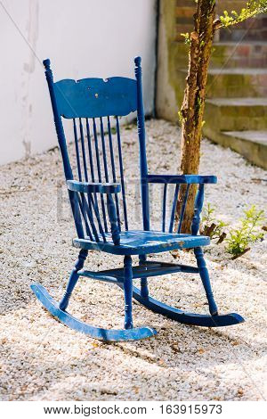 Blue antique rocking chairs on stone porch welcome visitors to sit and relax for a while