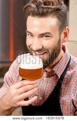 Close-up portrait of handsome brewer tasting beer in the glass