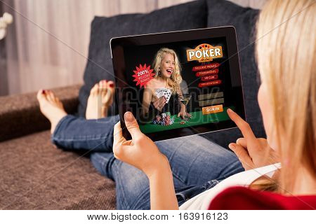 Woman playing poker on tablet computer at home