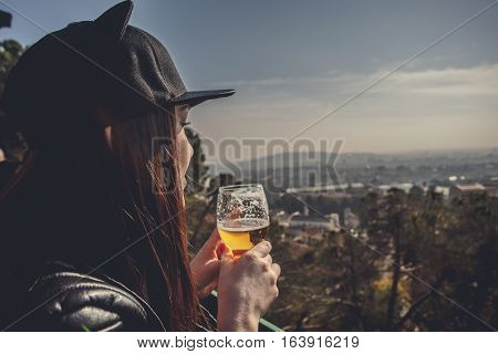 Side view of a young woman dressed standing and drinking alcohol . In the background landscape with aerial view clouds in the sky. Girl uses the gadget. Europa Barselona Spain. Old Building in Barcelona Spain. Top view of the city.