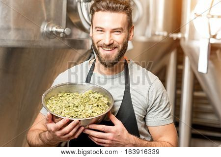 Portrait of a handsome brewer in uniform with hop in the bowl at the manufacturing with metal tanks