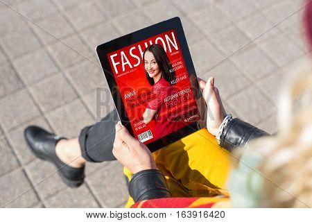 Woman reading fashion magazine on tablet computer