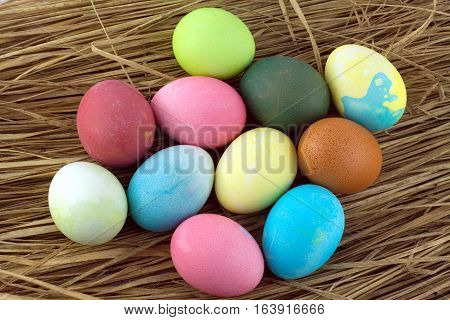 Many colorful Easter eggs on straw background closeup