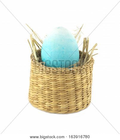 Color Easter egg inside small straw wicker brown basket isolate on white closeup