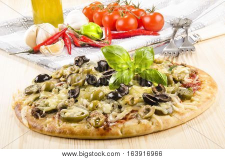 spicy italian pizza with olive basil and melted cheese on a wooden board