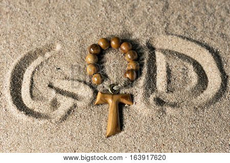 Tau wooden cross in the shape of the letter t with rosary bead and the written God in the sand