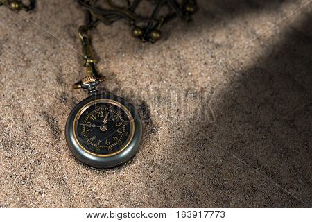 Old and small pocket watch with chain over the sand with dark shadows and a light beam