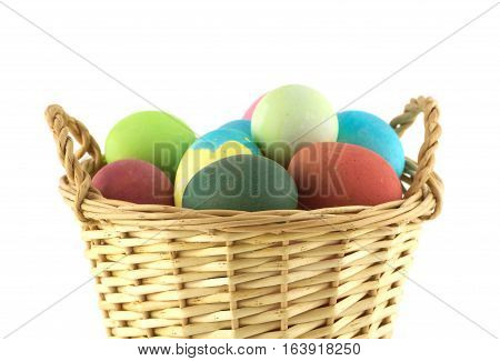 Colorful Easter eggs inside straw wicker brown basket front view isolate on white closeup