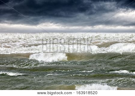 Stormy dark clouds in the sky over rough sea.