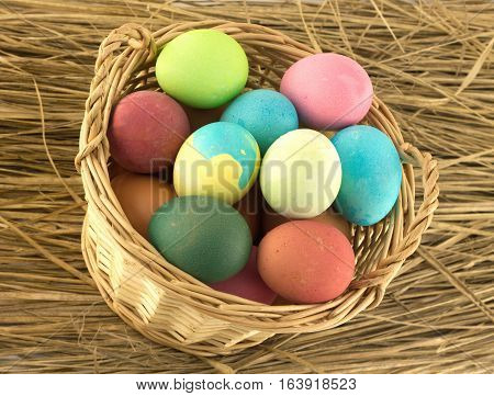Colorful Easter eggs inside wicker brown basket on straw background closeup