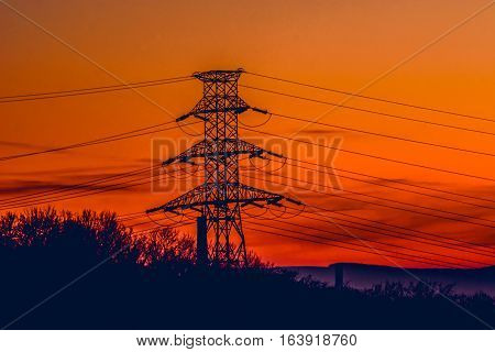 Electric pole with electrical wires in the sunset