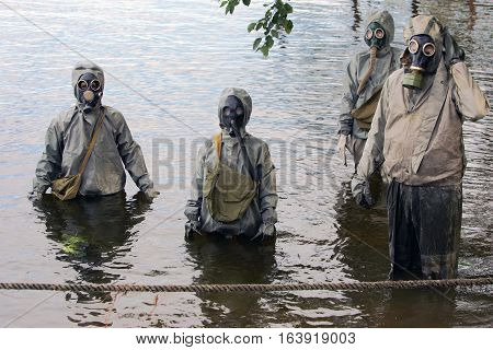 MOSCOW RUSSIA - SEPTEMBER 18.2004: People in protective suits and gas masks moving on the river for defensive teachings