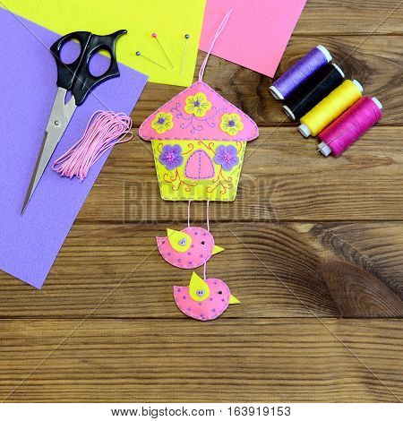 Wall decoration made from felt. Colourful house with birds and flowers. Scissors, felt sheets, colored thread, pin on wooden table. Easter wall decoration. Simple and beautiful craft project. Top view