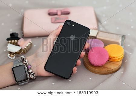 Alushta Russia - November 11 2016: Woman hand with Apple Watch holding iPhone 7. iPhone 7 Jet Black and Apple Watch was created and developed by the Apple inc.
