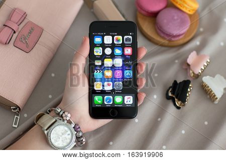 Alushta Russia - November 11 2016: Woman hand with Watch holding iPhone 7 Jet Black. iPhone 7 was created and developed by the Apple inc.