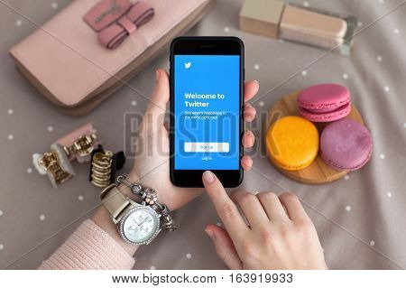 Alushta Russia - November 11 2016: Woman hand with Watch holding iPhone 7 Jet Black with social networking service Twitter on the screen. iPhone 7 was created and developed by the Apple inc.