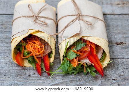 Various of tasty tortilla wraps on a wooden background. Healthy street food
