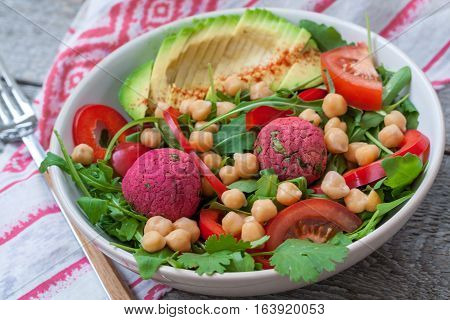 Vegan salad with falafel and vegetables. View top on dark wooden background. Vegan Food Concept.