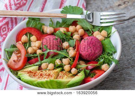 Vegan salad with falafel and vegetables. View top on dark wooden background. Vegan Food Concept.