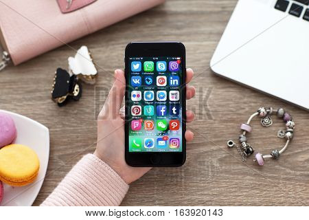 Alushta Russia - November 17 2016: A set of programs from famous brands of social networking on the iPhone 7 in woman hands. iPhone 7 Jet Black was created and developed by the Apple inc.