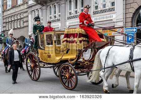 Copenhagen, Denmark - January 04, 2017: Queen Margrethe in her 24-carat golden coach is escorted by the Guard Hussar Regiment on the way from Christiansborg Palace to Amalienborg Palacce