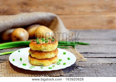 Roasted vegetable patties. Potato patties with vegetables and spices on plate and on wooden table. Raw potatoes, fresh green onions. Rustic style. Closeup. Tasty vegetarian recipe