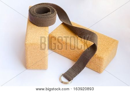 Yoga accessories. Two cork blocks and yoga strap on white background.