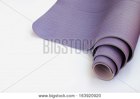 Yogi essentials.Modern lilac yoga mat on white background with copy space. Yoga practice concept.
