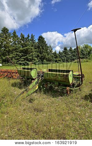 Old four corn planter with fertilizer boxes left discarded in a pasture