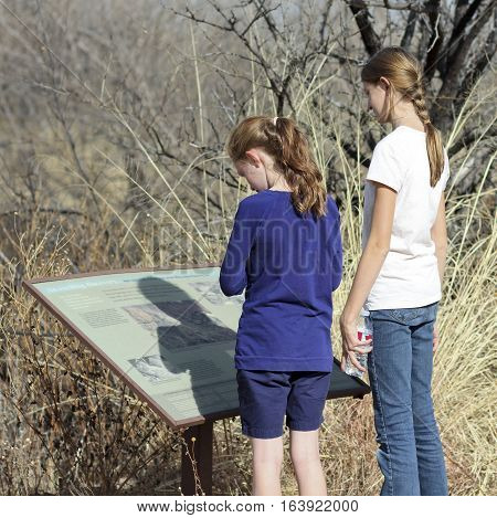 SIERRA VISTA, ARIZONA, DECEMBER 20. The Murray Springs Clovis Site on December 20, 2016, east of Sierra Vista, Arizona. A pair of sisters reads a sign at the Murray Springs Clovis Paleoindian Site.