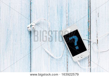 smartphone with earphone and question symbol on screen