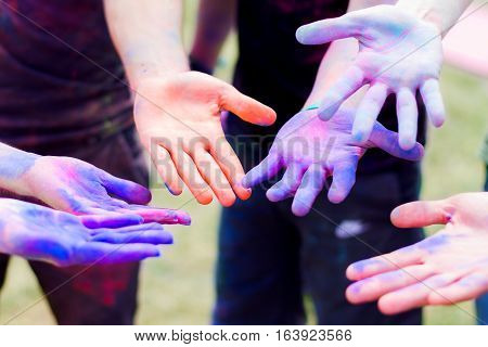 Close up shooting of hands holding colorful powder for Holi celebration