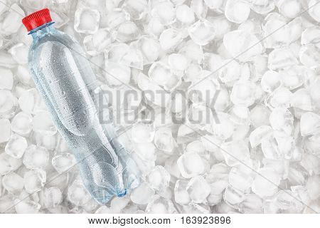 plastic water bottle with red cap is cooling in the ice
