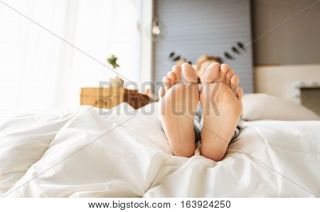 Rest and calm. Close up of young relaxed pregnant womans feet lying in bed while she having rest and enjoying happy times.