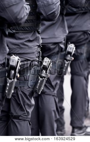 Special forces soldiers with pistols in scabbards during a military parade