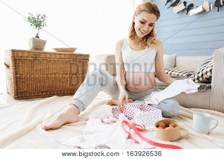 The cutest thing. Pregnant delighted young woman enjoying new baby clothes while smiling and sitting in a cozy room.