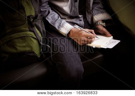 Young Man On A Train Writing Notes In Diary Or Journal. Backpacker Planning  On Notebook With Passpo