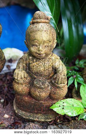 stone figurine a Buddhist drummer in the garden