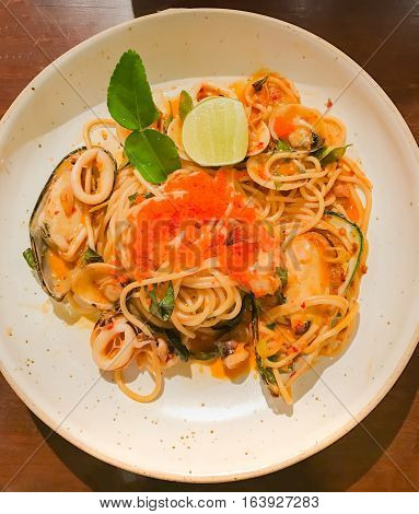 Seafood pasta Spaghetti with Clams Prawns squid. food on white plate closed up