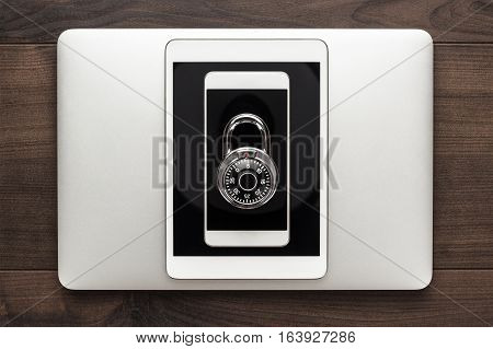 data security concept: computer, tablet, phone with combination lock on wooden table