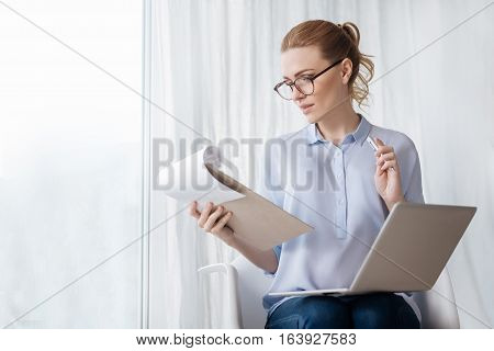 My responsibility. Pregnant beautiful young woman enjoying her work while using laptop and making notes on documents.