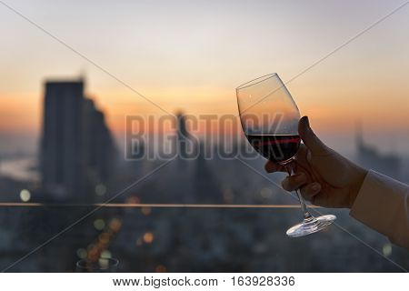 Closeup of a มglasses of red wine against night view of urban city sky line blurring lights.