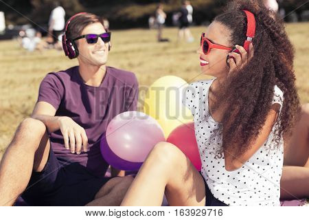 Afroamerican woman and handsome man wearing eyeglasses and headphones sitting on a grass in the park