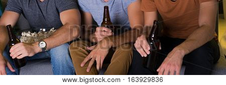 Men Sitting On A Couch With Beer