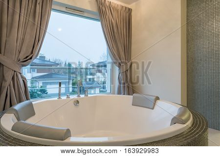 Well-lighted big bathroom with a luxurious jacuzzi