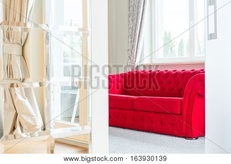 Bright room interior with red elegant couch